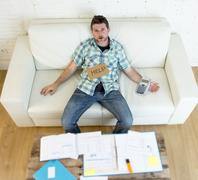 Young worried man at home sofa couch doing domestic debt accounting Stock Photos