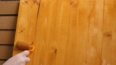 Hand with paint roller applying acrylic lacquer on wooden board - stock footage