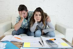 Young worried stressed couple at home couch doing domestic tax paperwork Stock Photos
