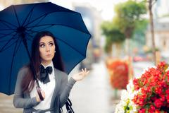 Curious Woman Holding  Umbrella Checking for Rain - stock photo