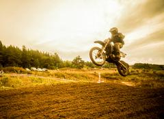 Boy mid air on motorcycle at motocross - stock photo