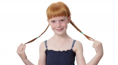 Close up little ginger girl is coquettishly touching her pigtails Stock Footage