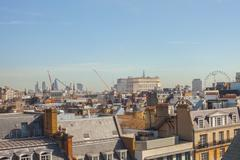 Rooftops and distant view of the millennium wheel, London, UK - stock photo