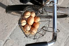 basket full of fresh eggs hen delivered on an old rusty bicycle - stock photo