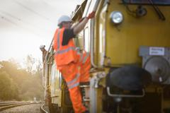 Railway worker climbing aboard maintenance train on railway Stock Photos