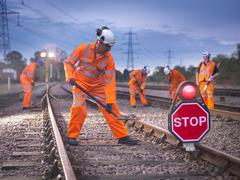 Railway maintenance workers on track with stop sign at night Stock Photos