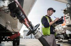 Male worker doing inspection at fuel depot - stock photo