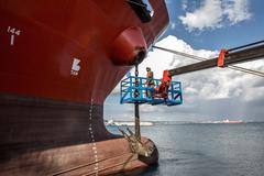 Worker on viewing platform inspecting oil tanker - stock photo