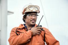 Worker on oil tanker using walkie talkie - stock photo