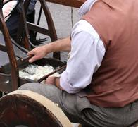 Elder carder while carding wool or cotton with old wooden machine - stock photo