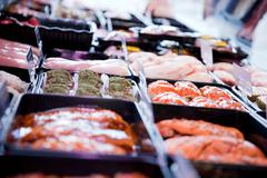 Variety of fresh meat products in refrigerator at butchers shop Stock Photos