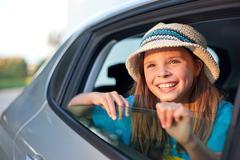 Girl wearing hat looking through open car window, smiling - stock photo