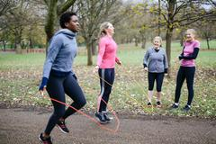 Women and teenager competing with skipping rope in park - stock photo