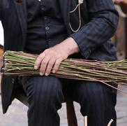 elderly man with a big and strong hand tightens the bundle of sticks - stock photo