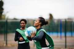 Young adult female netball player at play on netball court - stock photo
