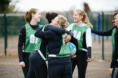 Female netball team celebrating on netball court - stock photo