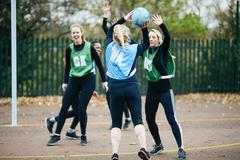 Female netball teams playing match on netball court - stock photo