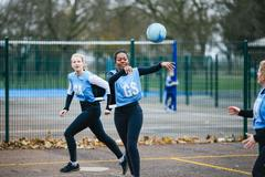 Female netball team playing match on netball court - stock photo