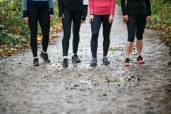 Waist down of teenage girl and women runners preparing to run in park - stock photo