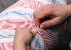 senior woman while sewing with needle and thread the old pillow - stock photo