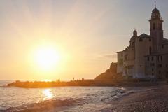 Sun rising over beach and ornate church Stock Photos