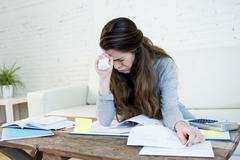 Young worried woman suffering stress doing domestic accounting paperwork bill Stock Photos