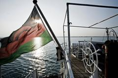 Mozambique flag flying from boat - stock photo