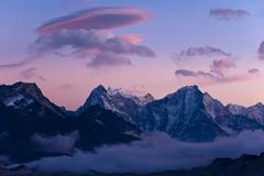 Snowy mountaintops and clouds - stock photo