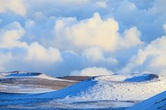 Snowy hilltops and clouds - stock photo