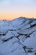 Sun rising over snowy mountaintops - stock photo