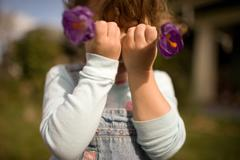 Young girl holding flowers in front of face Stock Photos