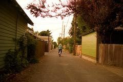 Boy cycling down alleyway - stock photo