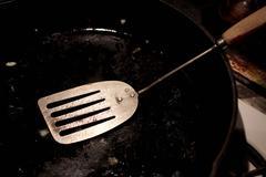 Spatula in empty frying pan - stock photo