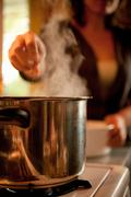 Person cooking with saucepan on hob Stock Photos
