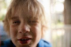 Young boy looking through door screen - stock photo