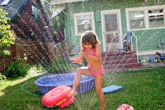 Young girl playing in garden sprinkler - stock photo