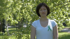 Young woman with green awareness ribbon - stock footage
