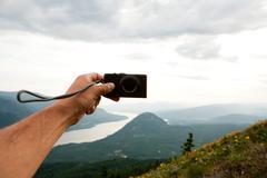 Man photographing self in rural scene - stock photo
