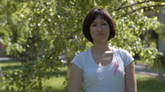 Young woman with pink awareness ribbon Stock Footage