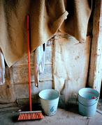Broom and buckets in stable - stock photo