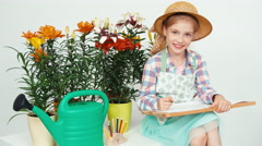 Close-up portrait child girl sitting near flowers and drawing on drawing board - stock footage