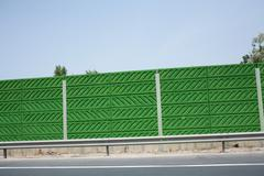 Green wall by road - stock photo