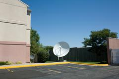Satellite dish in parking lot - stock photo