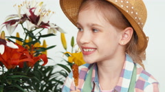 Close-up portrait flower-girl child in hat sitting near flowers - stock footage