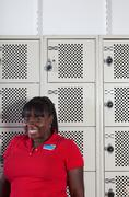 Young retail assistant in locker room, smiling - stock photo