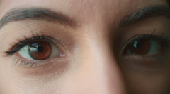 A woman's brown eyes blinking and creasing to smile, detail Stock Footage