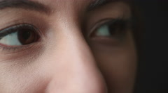 Woman's brown eyes moving, and creasing to smile, side view Stock Footage
