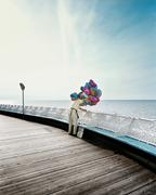 Man selling helium balloons at seaside Stock Photos
