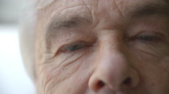 Close up of Senior Man's face blinking and smiling Stock Footage