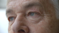 Senior man's face looking at camera, blinking, detail Stock Footage